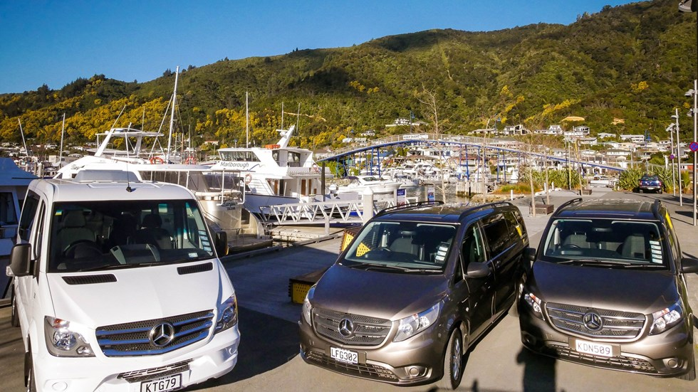 Marlborough Tour Company vehicles parked beside seafood cruise vessels in Picton, New Zealand.