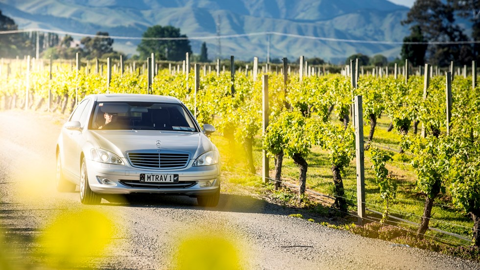 Silver car drives alongside a vineyard with hills in the background as part of a private wine tour in Marlborough near Blenheim, at the top of New Zealand's South Island