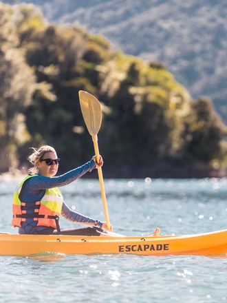 A women admires the view while kayaking around Punga Cove in the Marlborough Sounds in New Zealand's top of the South Island