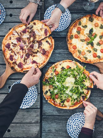 A group of friends share three hot stone baked pizzas and drinks from the Boatshed Cafe and Bar at Punga Cove located in the Marlborough Sounds of New Zealand's South Island