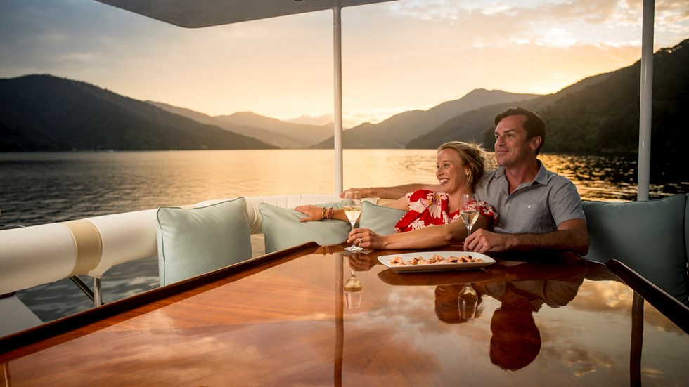 Couple sits on a boat at a table with wine enjoying the sunset over the Marlborough Sounds, at the top of New Zealand's South Island