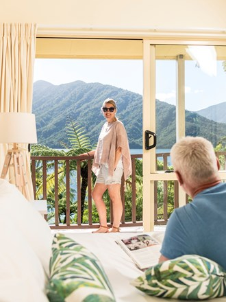 Couple relax in their Frond Suite room and balcony with scenic Endeavour Inlet background views at Punga Cove in the Marlborough Sounds in New Zealand's top of the South Island