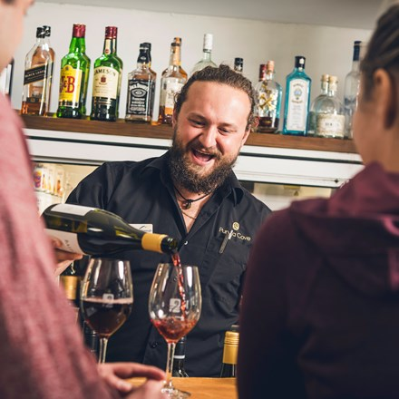 A friendly bartender pours Pinot Noir into glasses for customers at the Boatshed Cafe and Bar at Punga Cove - choose from a great range of local craft beer, wine , cocktails, soft drinks and expresso coffee.