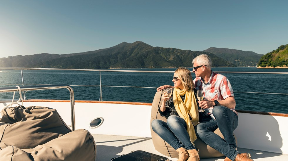 Couple sit at the bow onboard a Marlborough Tour Company boat in the Marlborough Sounds at the top of New Zealand's South Island with glasses of wine looking at the view