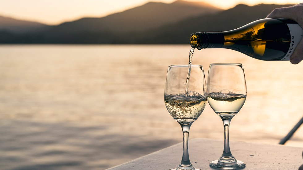 Wine bottle pouring white wine into two glasses at sunset onboard a boat in the Marlborough Sounds, at the top of New Zealand's South Island.