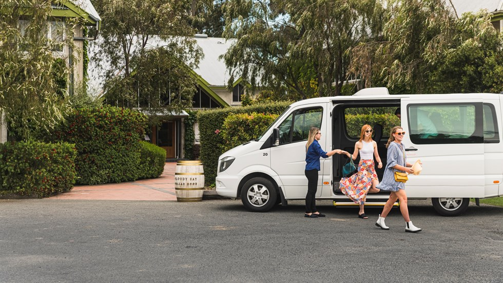 Two women are helped out of a van by a Marlborough Tour Co staff member on a wine tour at a winery cellar door in Marlborough, at the top of New Zealand's South Island