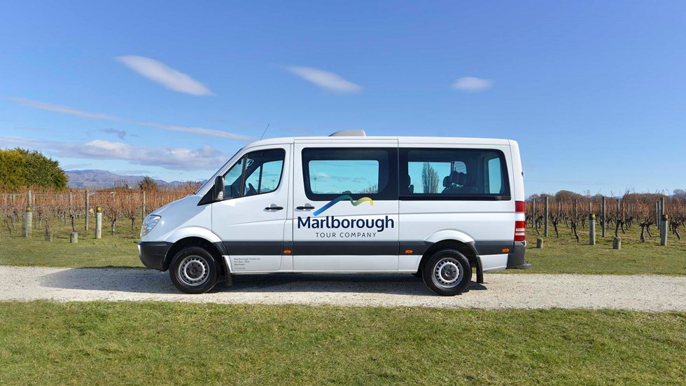 Close up of white van parked in vineyard on a Marlborough Tour Company wine tour, near Blenheim in Marlborough at the top of New Zealand's South Island.