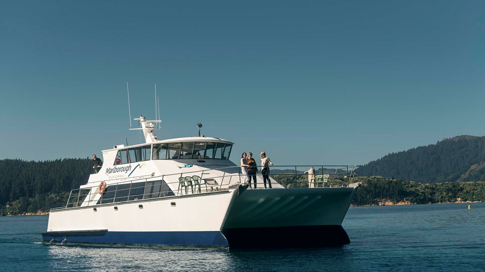 Close up of MV Odyssea with people on the bow cruising the Marlborough Sounds, at the top of New Zealand's South Island