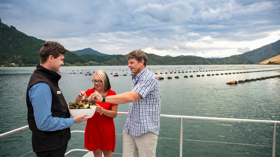 A couple taste steamed fresh Greenshell mussels, served at the source on a Seafood Odyssea cruise in New Zealand's Marlborough Sounds from Picton.