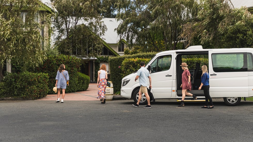 Group of four exiting a van and walking into a winery cellar door on a wine tour in Marlborough, at the top of New Zealand's South Island