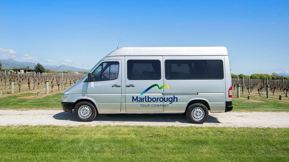 Silver van with Marlborough Tour Company logo on side parked in vineyard, near Blenheim in Marlborough at the top of New Zealand's South Island.