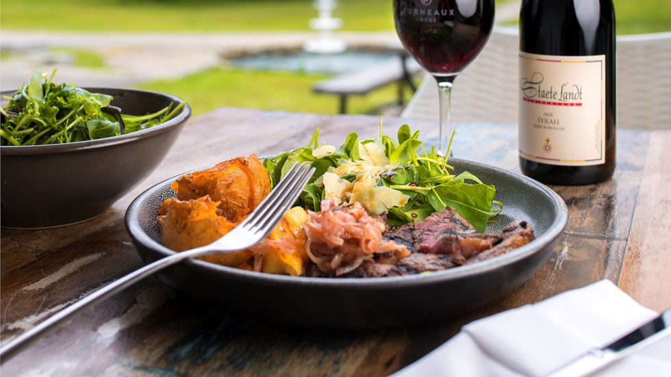Gourmet steak, potato and salad meal served with ocean view and glass of Staete Landt Syrah at the Furneaux Lodge Restaurant in the Marlborough Sounds at the top of New Zealand's South Island.