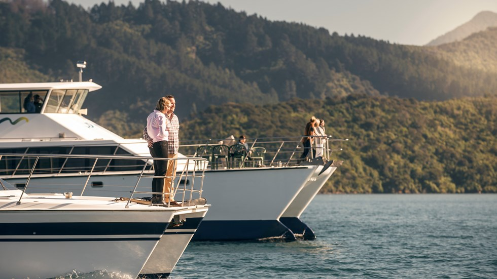 Two launches next to each other with passengers on the bow cruising in the Marlborough Sounds at the top of New Zealand's South Island.,